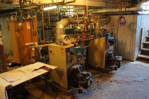 Before Image showing the old boilers and cluttered piping prior to gas conversion